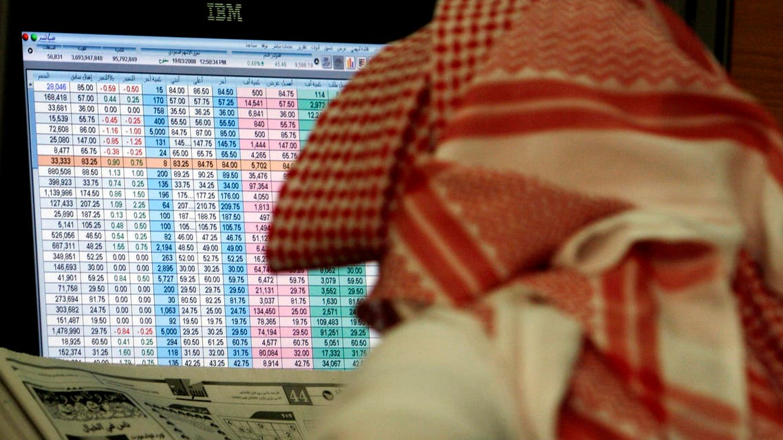 A Saudi man reads a newspaper while keeping an eye on a screen displaying stock market figures, Wednesday, March 19, 2008, at al Jazeera Capital Bank in Riyadh, Saudi Arabia. The declining U.S. economy is affecting dollar-pegged Persian Gulf countries. (AP Photo/Hasan Jamali)