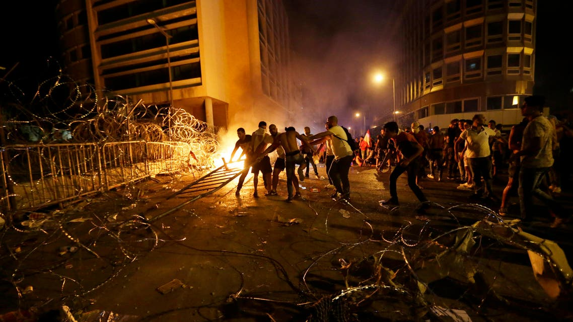 In this Tuesday, Aug. 25, 2015, file photo, Lebanese protesters set fire to barriers and trash behind the barbed wire separating them from the police, during a protest against the trash crisis and government corruption, in downtown Beirut, Lebanon. (AP Photo/Hassan Ammar, File)