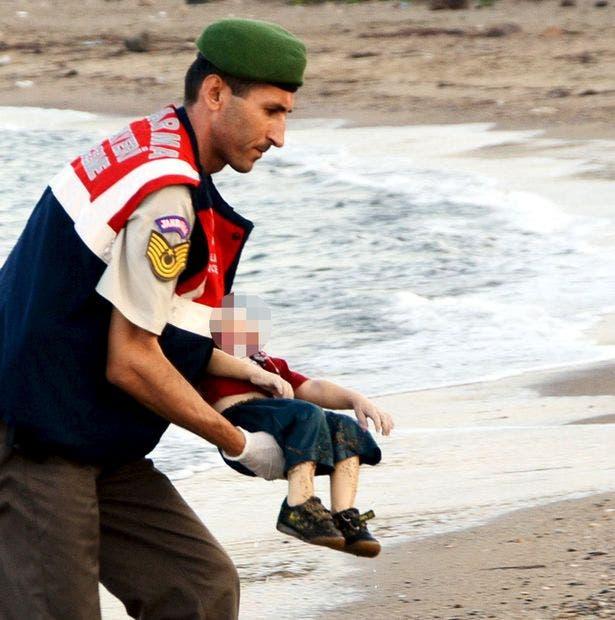 شامی بچے ایلان کردی کی لاش کو ایک ترک پولیس اہلکار نے اٹھایا ہوا ہے۔