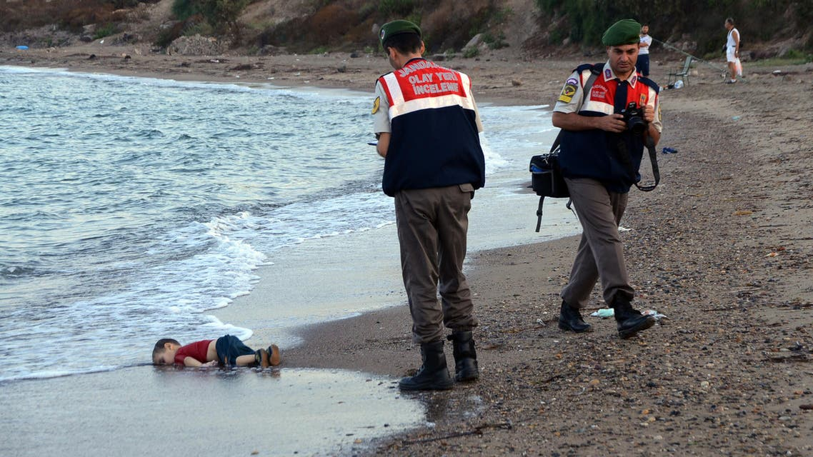 Paramilitary police officers investigate the scene before carrying the lifeless body of Aylan Kurdi, 3, AP