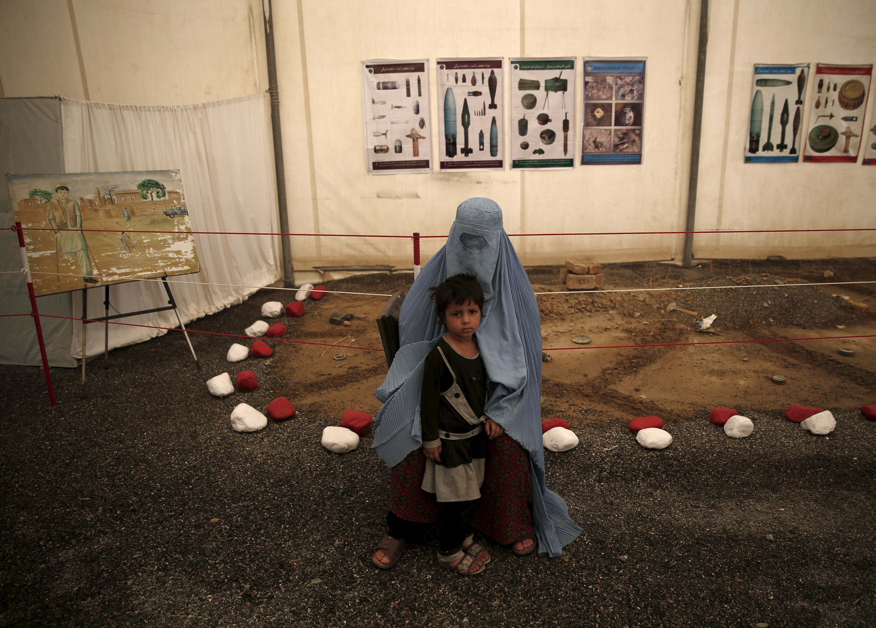 An Afghan refugee woman, clad in a burqa, sits with her child after arriving at a United Nations High Commissioner for Refugees (UNHCR) registration centre in Kabul, Afghanistan August 26, 2015.