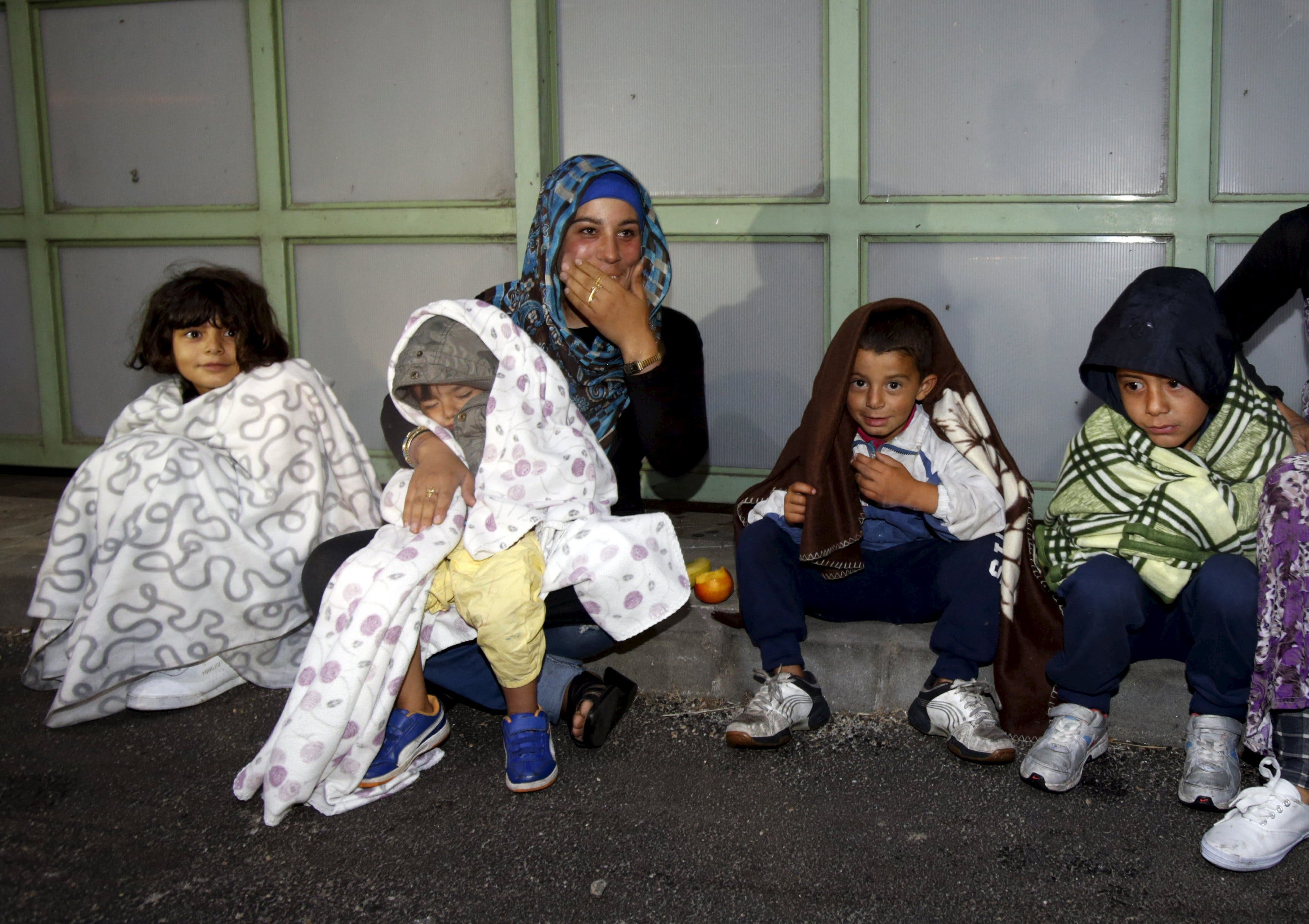 Migrants sit at the Austrian-Hungarian border station of Hegyeshalom, Hungary, September 5, 2015. (Reuters)