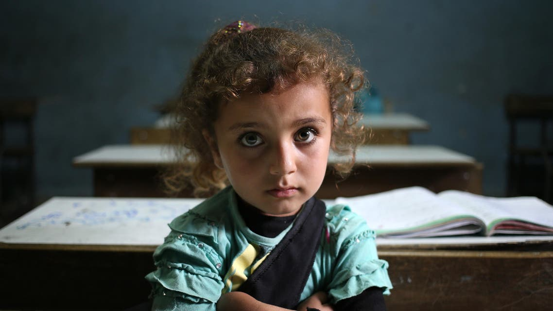 In this Thursday, May 29, 2014 file photo, a Syrian refugee girl sits in a classroom at a Lebanese public school where only Syrian students attend classes in the afternoon, at Kaitaa village in north Lebanon. AP