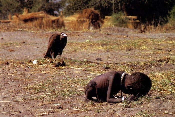 A vulture stalks a toddler in southern Sudan as her parents get food from a United Nations plane in 1993. (Photo courtesy: Kevin Carter/ The New York Times)