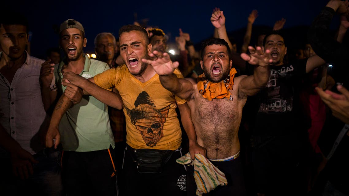 Refugees and migrants take part in a protest demanding the authorities to let them go to Athens and continue their trip towards Northern Europe, at the port of Mytilene, on the northeastern Greek island of Lesbos, on Saturday, Sept. 5, 2015. (AP)