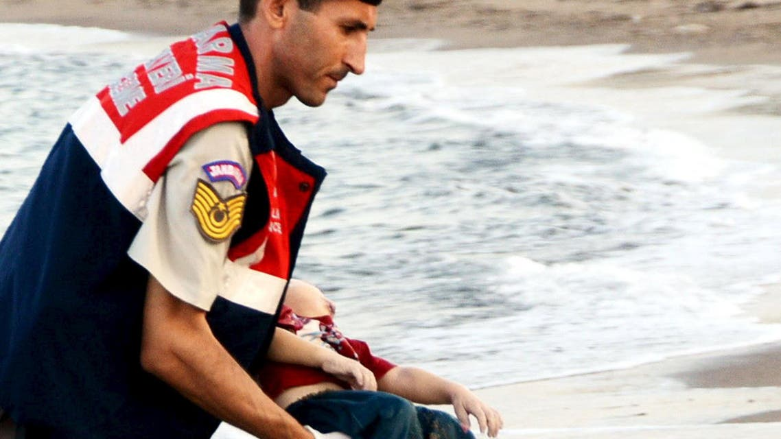 Turkish gendarmerie carries a young migrant, who drowned in a failed attempt to sail to the Greek island of Kos, in the coastal town of Bodrum, Turkey, September 2, 2015. REUTERS