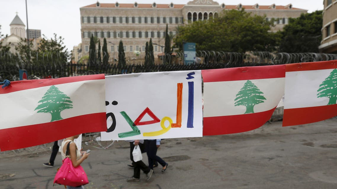 People walk near barbed wire and national flags a day after protests against the government in Beirut. (Reuters)