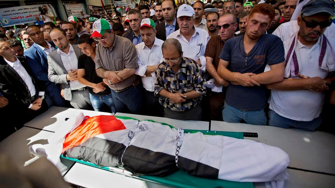 Palestinians prays by the body of Saed Dawabsheh, 32, during his funeral procession in the West Bank village of Duma near Nablus on Saturday, Aug. 8, 2015. (AP)