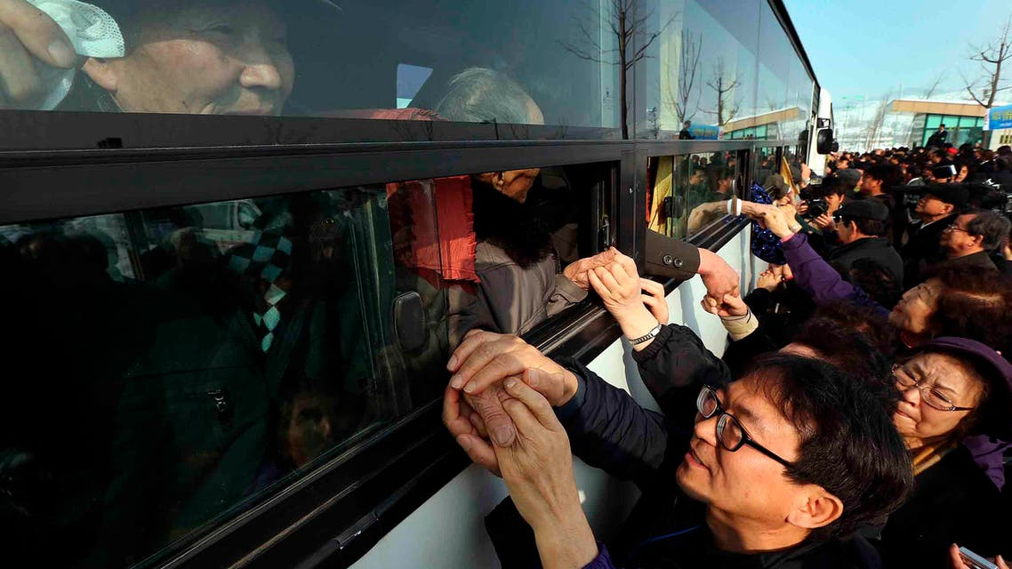 South Koreans hold their North Korean relative's hands on a bus after the Separated Family Reunion Meeting at Diamond Mountain in North Korea.