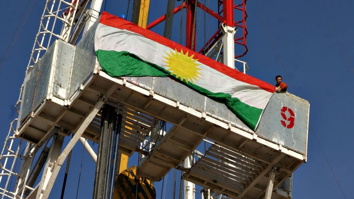 A Chinese worker hangs the flag of the Kurdistan Regional Government atop the drill of Norwegian Public Oil company DNO, that started drilling for oil in Iraqi Kurdistan, near Zakho, Nov. 29, 2005. (File photo: AP)