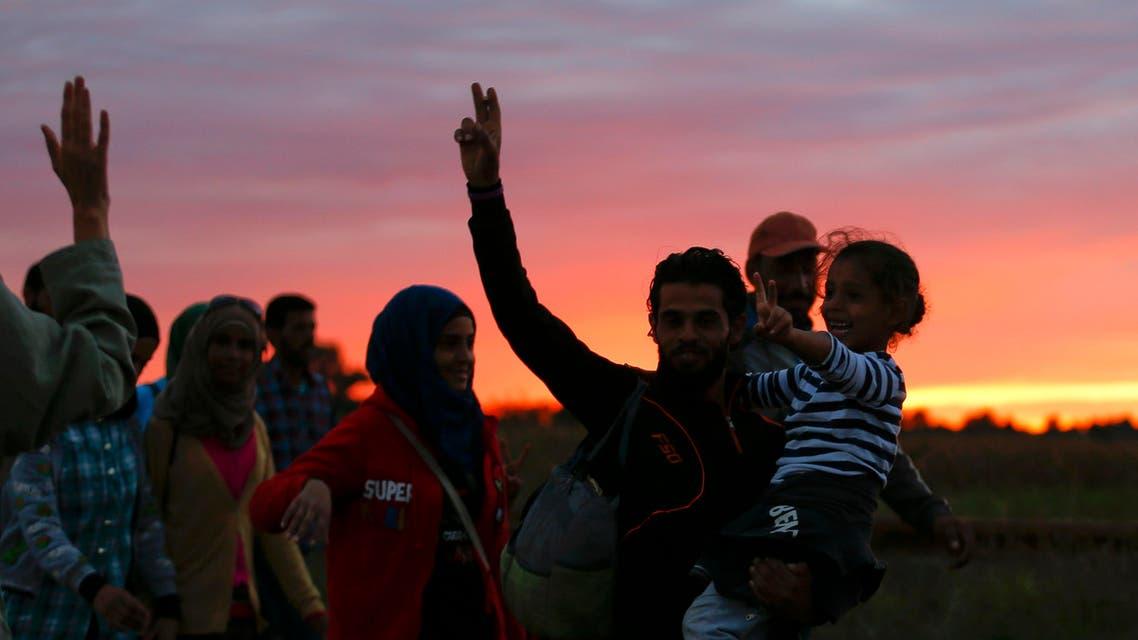Migrants arrive at sunset to a collection point in the village of Roszke