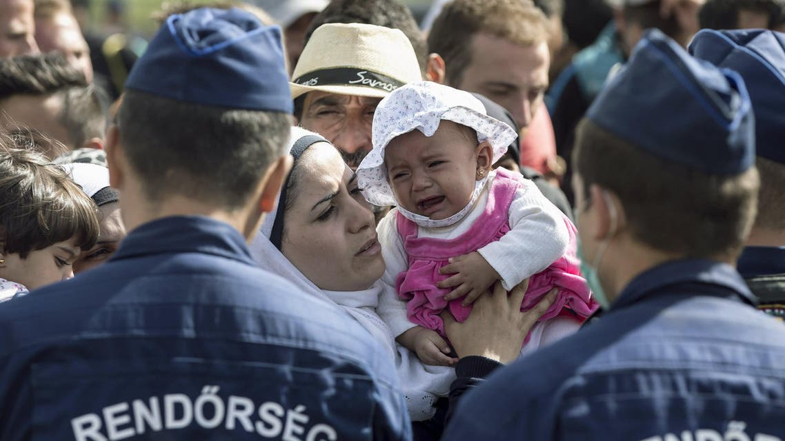 A migrant kisses a child who is crying as they stand in front of Hungarian police officers while waiting to board buses at a collection point in the village of Roszke, Hungary, September 7, 2015. Reuters