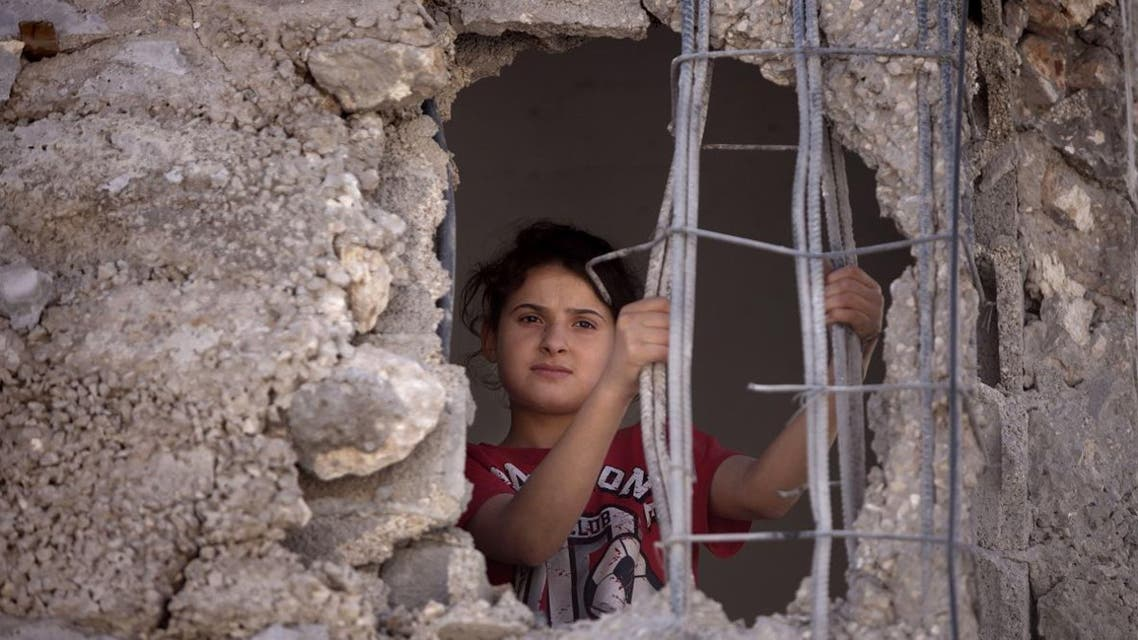 Mai Awad looks out from the damaged family home of Palestinian Ziad Awad in the town of Idna,13 kilometers (8 miles) west of the West Bank city of Hebron, Wednesday, July 2, 2014.