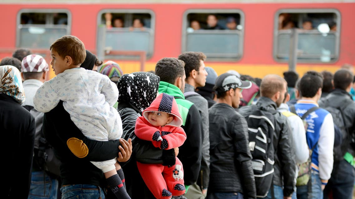 People stand in a queue as they prepare to leave by train from the southern Macedonian town of Gevgelija,Tuesday, Sept. 8, 2015. Hundred of thousands migrants and refugees trying to reach the heart of Europe via Turkey, Greece, the Balkans and Hungary have faced dangers, difficulties and delays on every link of the journey. (AP Photo/Borce Popovski)