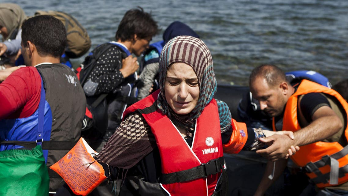 A Syrian refugee wearing a life jacket and armbands reacts moments after arriving on a dinghy on the Greek island of Lesbos. (Reuters)
