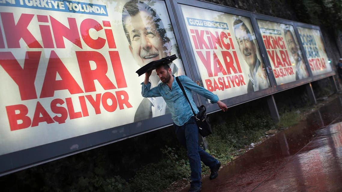 Under heavy rain, a man walks past billboards of Turkey's Prime Minister and leader of the Justice and Development Party (AKP) Ahmet Davutoglu in Istanbul, Turkey, Friday, June 5, 2015. (AP)
