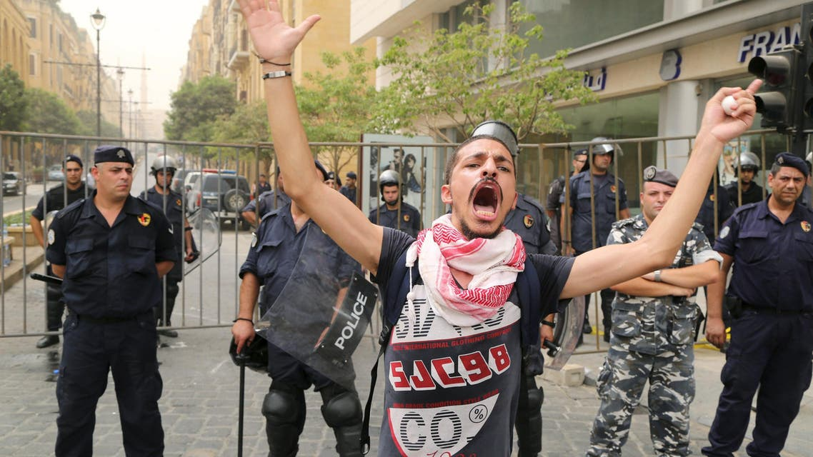 """A protester gestures in front of policemen blocking a street leading to the parliament building where a session of """"national dialogue"""" is taking place between politicians aimed at discussing ways out of a political crisis, in downtown Beirut, Lebanon September 9, 2015. Lebanese security services locked down central Beirut on Wednesday as politicians gathered to discuss ways out of the political crisis that has paralysed government and fueled a wave of street protests. Activists mobilizing against government failures including a waste disposal crisis that has allowed garbage to pile up in Beirut have called protests to coincide with the """"national dialog"""" called by parliamentary speaker Nabih Berri. REUTERS/Aziz Taher"""