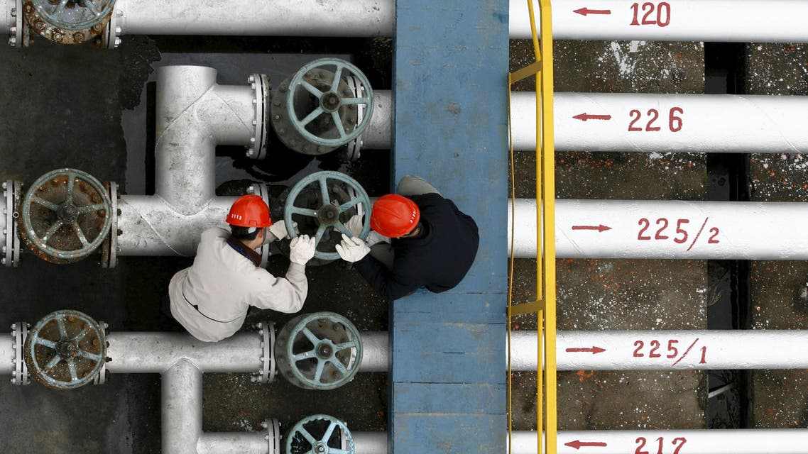Labourers work at a refinery in Jingmen, in central China's Hubei province, in this December 8, 2006 file photo.
