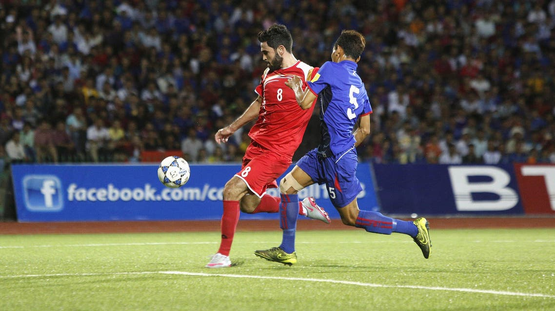 Syria's Omar Kharbin (L) fights for the ball with Cambodia's Soeuy Visal during their 2018 World Cup qualifying soccer match in Phnom Penh September 8, 2015. REUTERS/Samrang Pring