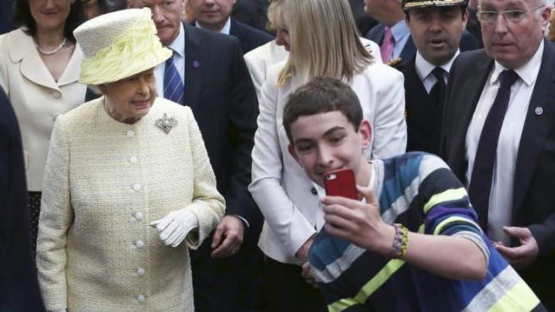 A local youth takes a selfie in front of Britain's Queen Elizabeth in St George's indoor market in Belfast, Northern Ireland June 24, 2014. (AP)