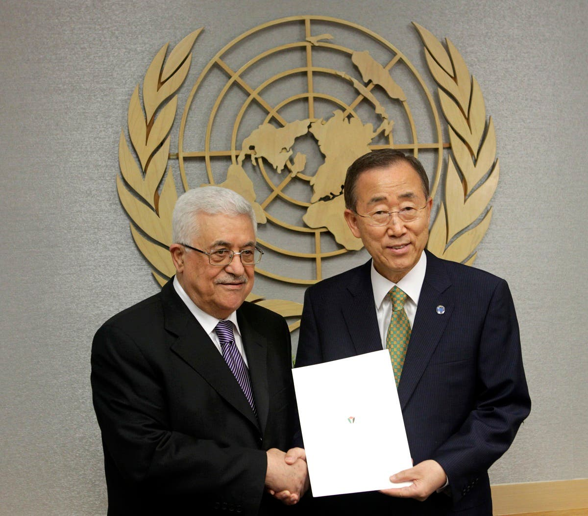 Palestinian President Mahmoud Abbas, left, poses for a picture with Secretary-General Ban Ki-moon after giving him a letter requesting recognition of Palestine as a state during the 66th session of the General Assembly at United Nations headquarters Friday, Sept. 23, 2011.