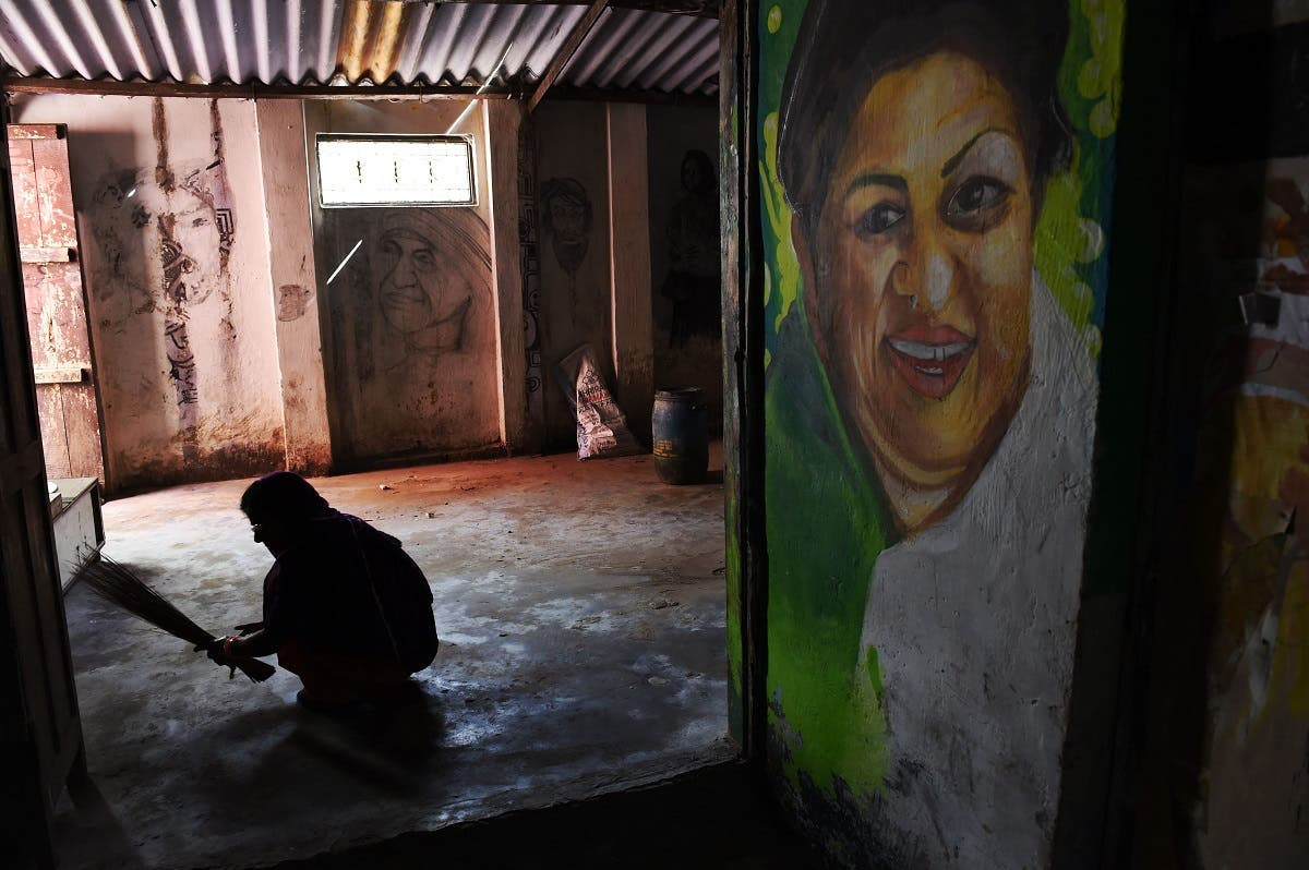 an Indian woman sweeps the floor of a room adorned by a student's painting of famous Indian singer Lata Mangeshkar afp