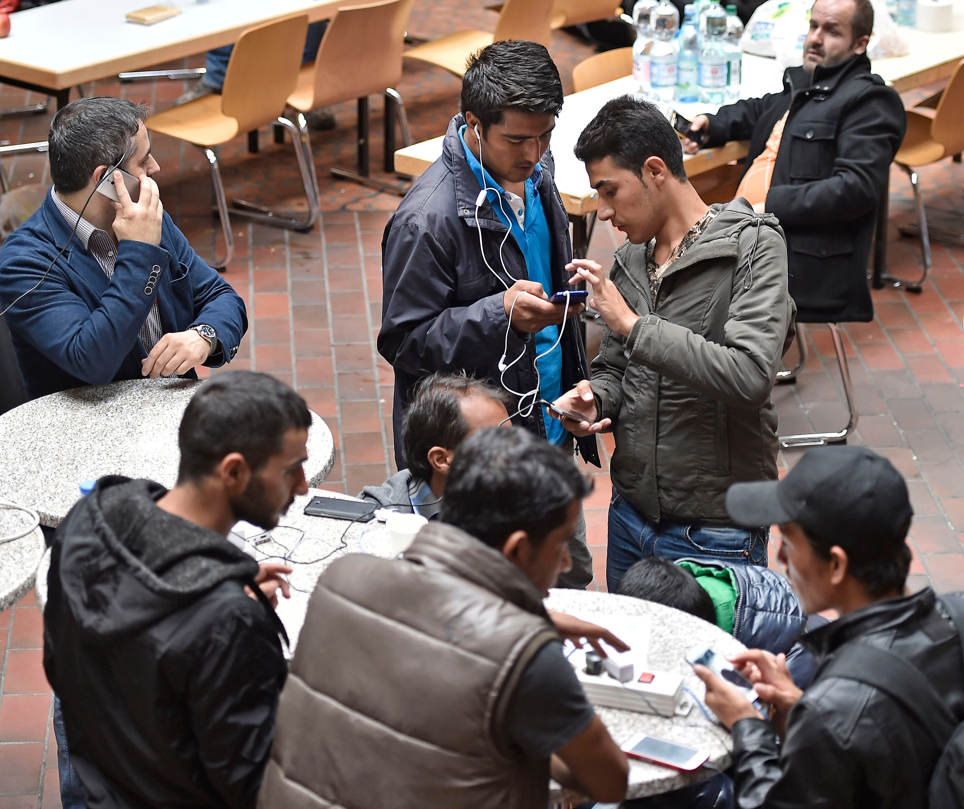 Migrants using their smartphones as they wait for transport to an asylum seekers facility in Dortmund, Germany,