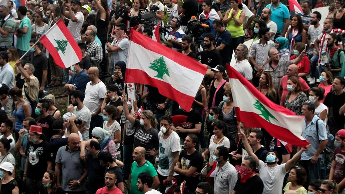 Lebanese anti-government protesters shout slogans as they hold their national flags, during a protest against the on-going trash crisis and government corruption, in downtown Beirut. (AP)
