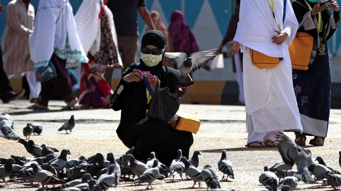 Muslim pilgrims picturing pigeorons wear surgical masks to prevent infection fm respiratory virus known as MERS in the holy city of Mekkah. (File photo: AP)