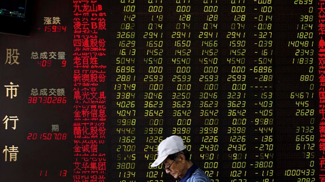 A man walks past an electric board displaying stock prices at a brokerage house in Beijing. (AP)