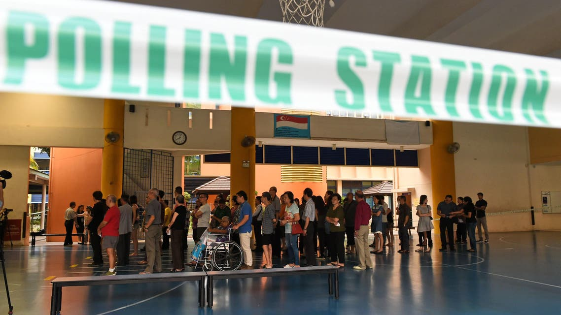Singaporeans queue at a polling station to cast their votes in Singapore on September 11, 2015.