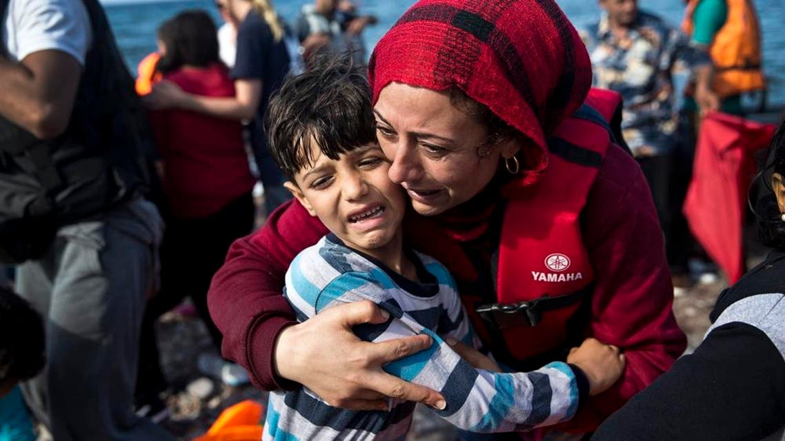 A Syrian woman embraces her child after they arrived with others migrants on a dinghy from Turkey to Lesbos island, Greece, Friday, Sept. 11, 2015. While migrants for years have taken death-defying trips across the Mediterranean to reach the relative peace and comfort of the Europe Union, the flow has hit record proportions this year - notably with an influx of Syrians, Afghans and Eritreans fleeing trouble back home. (AP Photo/Petros Giannakouris)