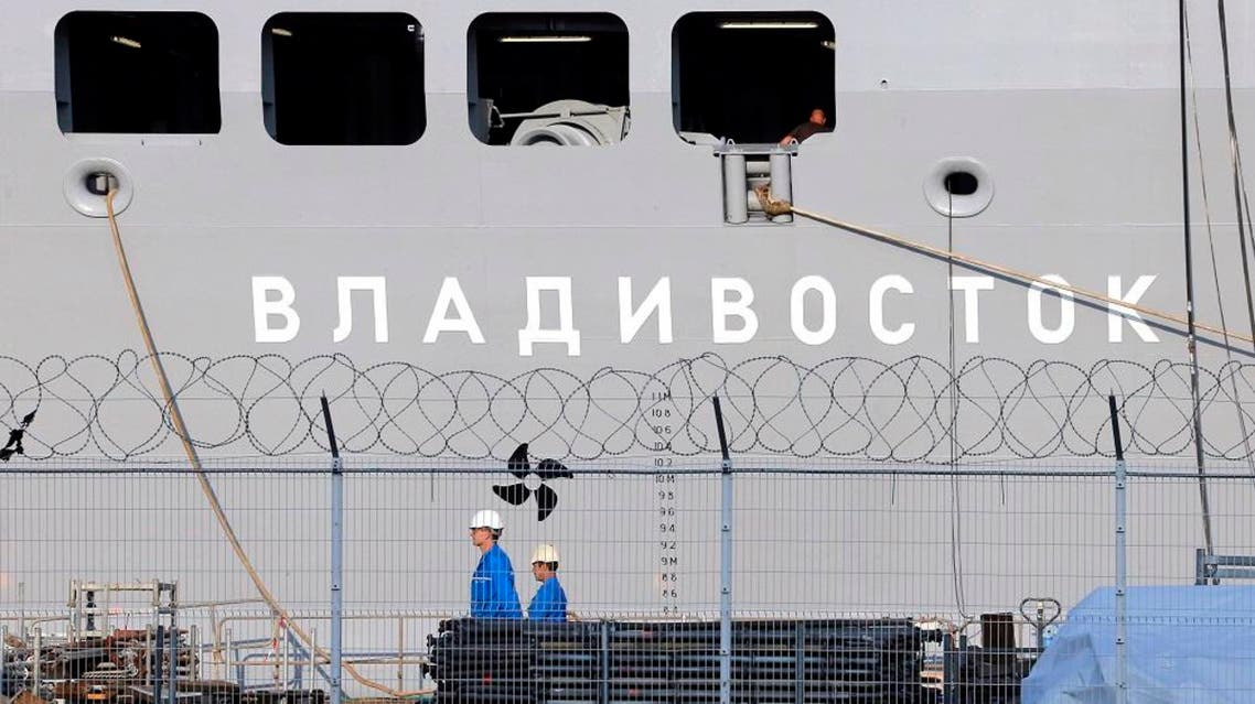 In this Sept.5, 2014 file photo, workers walk past the the Vladivostok warship on the port of Saint-Nazaire, western France. France will refund 950 million euro ($1 billion) to Russia for the cancellation of the sale of two Mistral-class warships, but avoid paying penalties. (AP Photo/David Vincent, File)