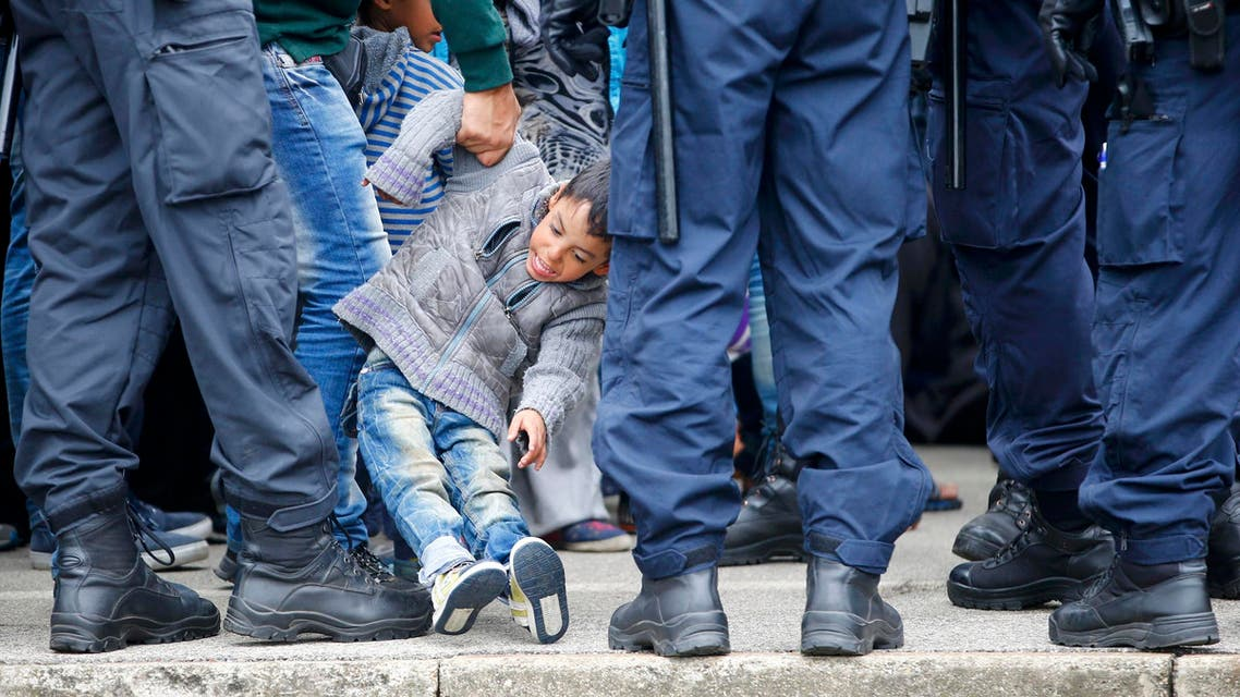 A migrant pulls a child away from the edge of the platform at the train station in Nickelsdorf, Austria, September 11, 2015. (Reuters)