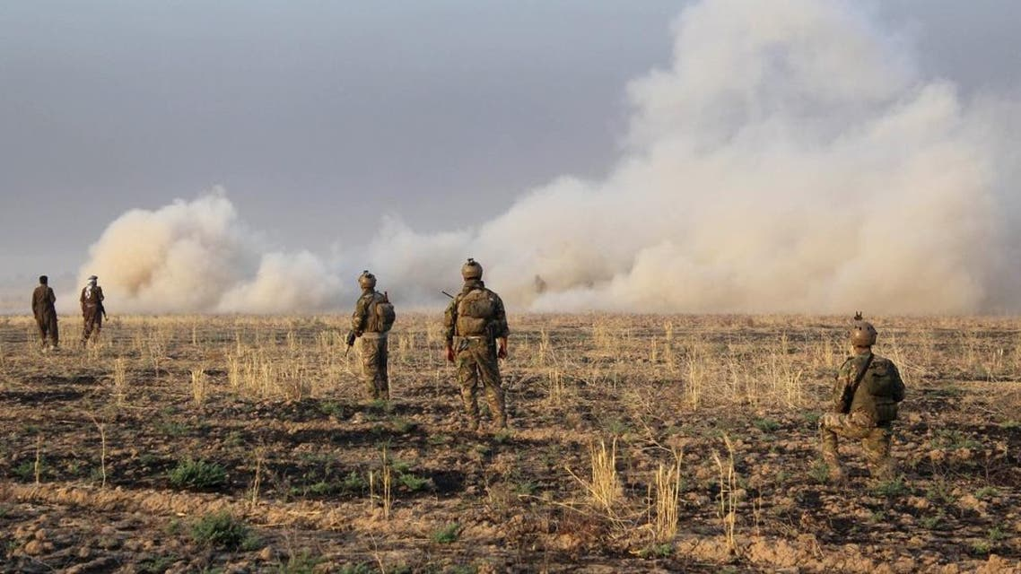 Kurdish Peshmerga fighters walk with their weapons as smoke rises from a site of clashes south of Daquq, north of Baghdad. (File: Reuters)