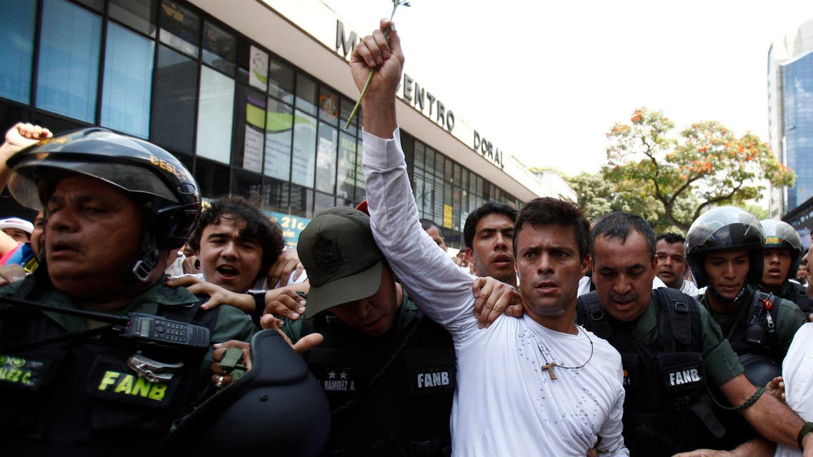 Opposition leader Leopoldo Lopez, dressed in white and holding up a flower stem, is taken into custody by Bolivarian National Guards,