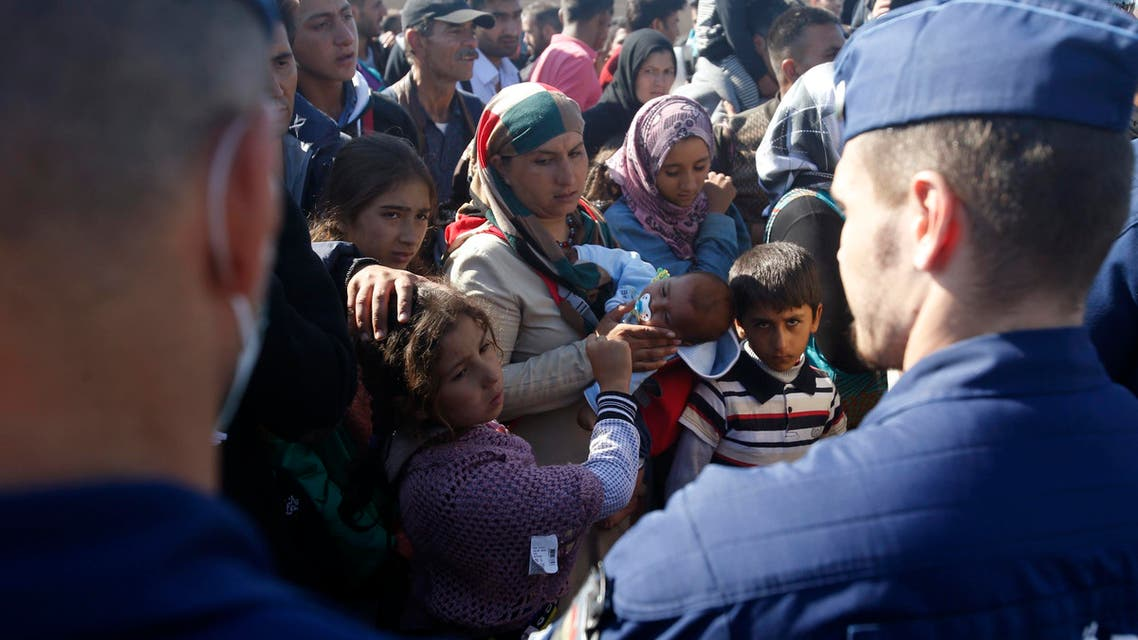 Migrants waiting for the bus that will take them to the center for asylum seekers near Roszke, southern Hungary, Wednesday, Sept. 9, 2015. AP