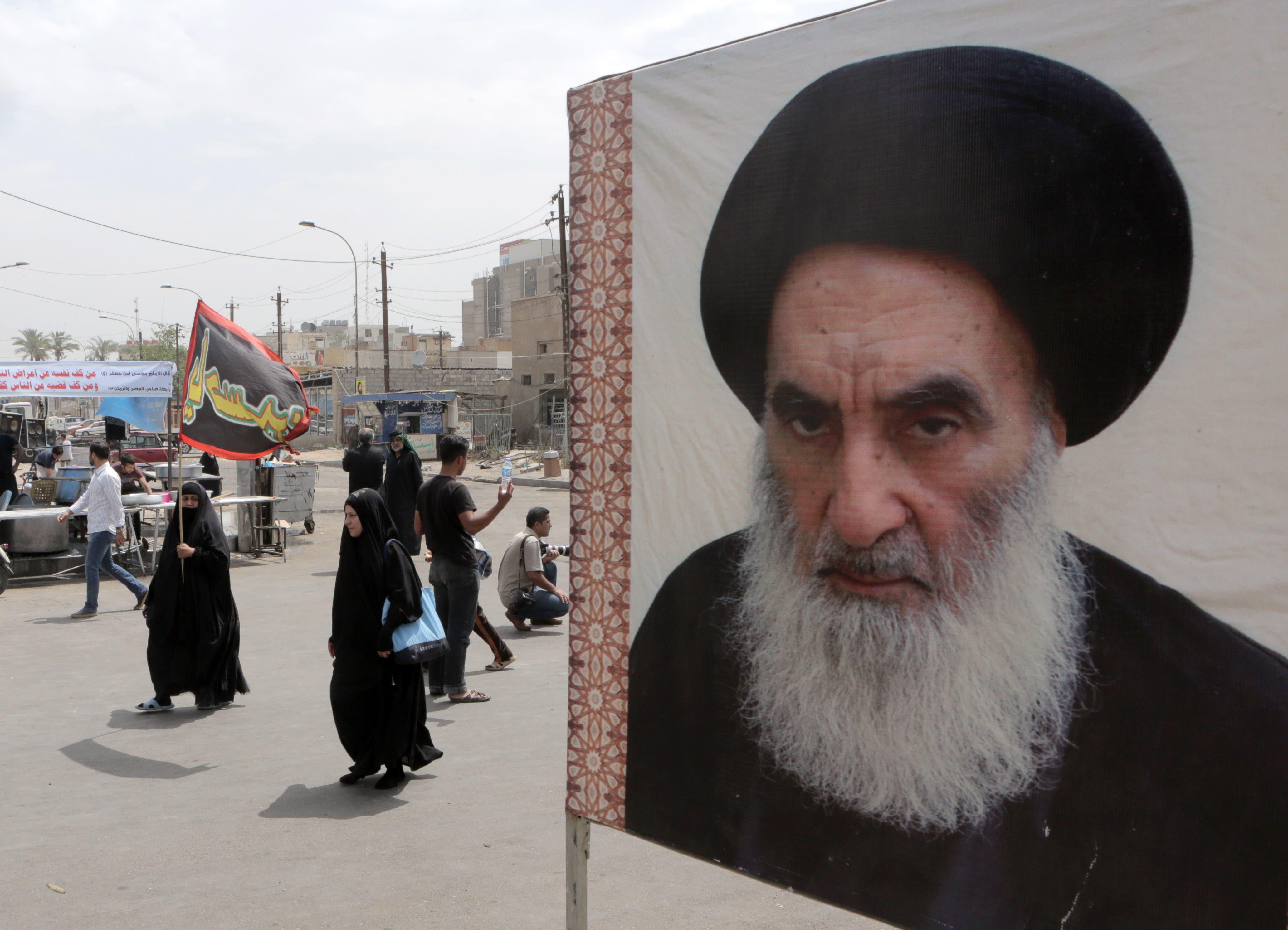 A poster of Shiite spiritual leader Grand Ayatollah Ali al-Sistani, right, in Baghdad, Iraq, Thursday, May 22, 2014. (File photo: AP)