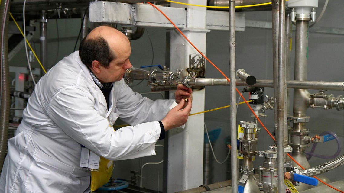 An unidentified International Atomic Energy Agency (IAEA) inspector cuts the connections between the twin cascades for 20 percent uranium enrichment at the Natanz facility, some 200 miles (322 kilometers) south of the capital Tehran,