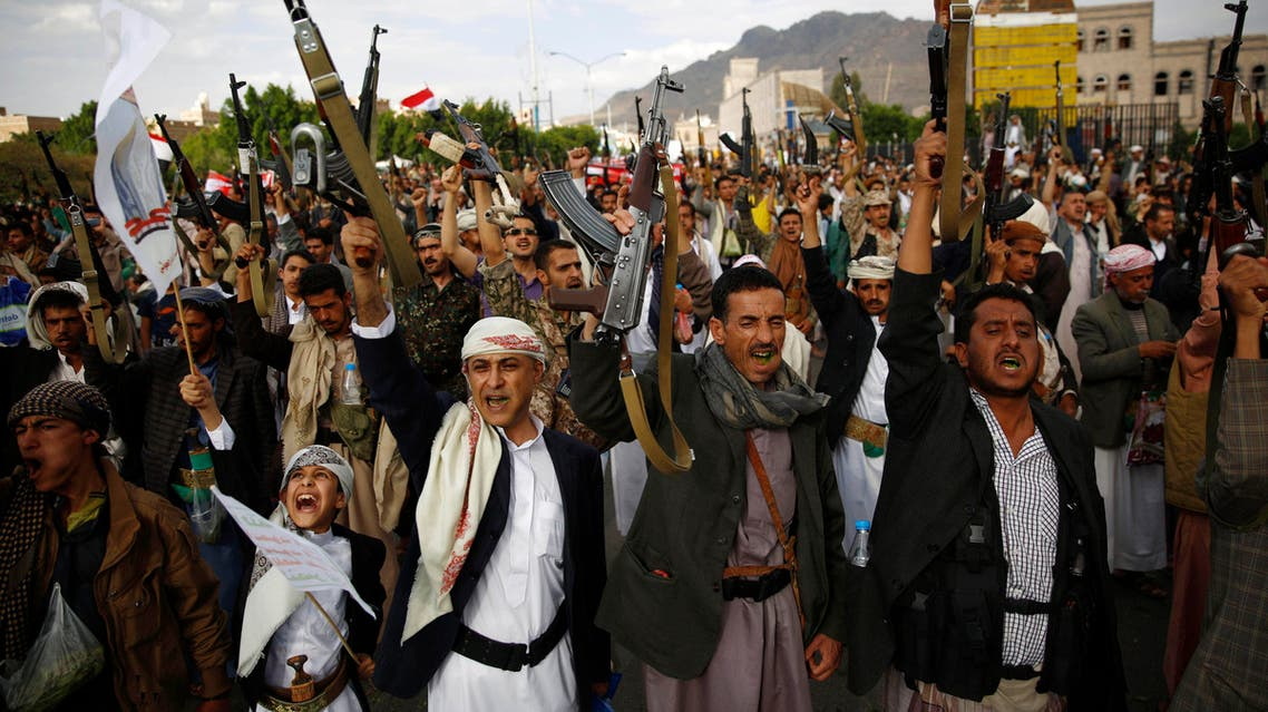 Shiite rebels known as Houthis hold up their weapons as they chant slogans during a rally