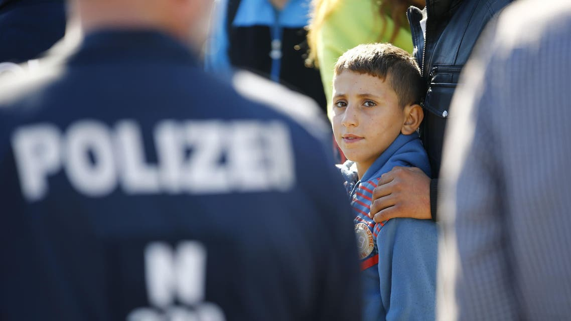 A migrant boy waits for a bus at the crossing point between Hungary and Austria in Nickelsdorf, September 12, 2015.