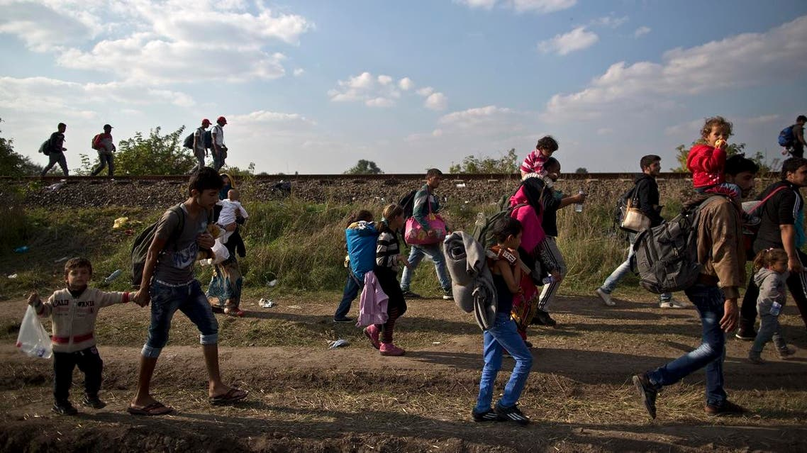 Migrants make their way through a field and a railway track after crossing the border between Serbia and Hungary in Roszke, southern Hungary, Sunday, Sept. 13. (AP)