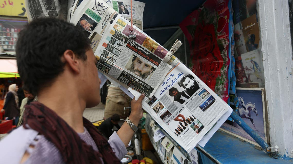 In this Aug. 1, 2015 file photo, an Afghan reads local newspapers carrying headlines about the new leader of the Afghan Taliban, Mullah Akhtar Mansoor, and former leader Mullah Mohammad Omar who was declared dead, on display at a newsstand in Kabul, Afghanistan.