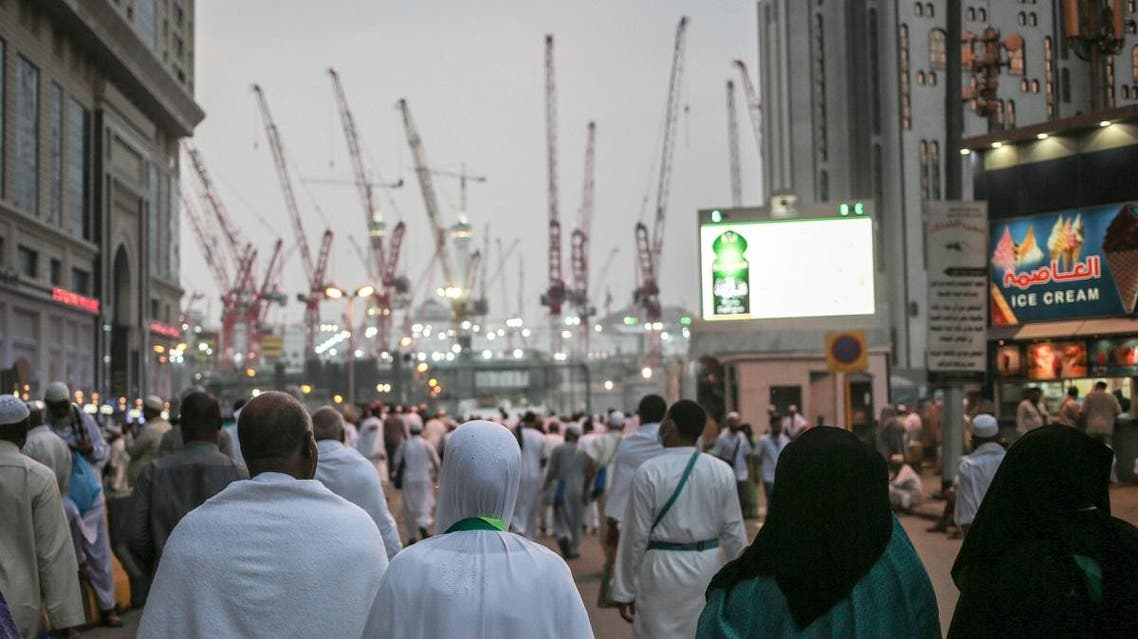 Muslim pilgrims walk towards the Grand Mosque in the holy city of Makkah, Saudi Arabia, marked by towering cranes used in the ongoing expansion. (AP)