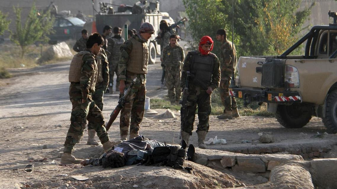 Afghan National Army (ANA) soldiers stand over the body of a Taliban insurgent outside a prison in Ghazni, Afghanistan, September 14, 2015.