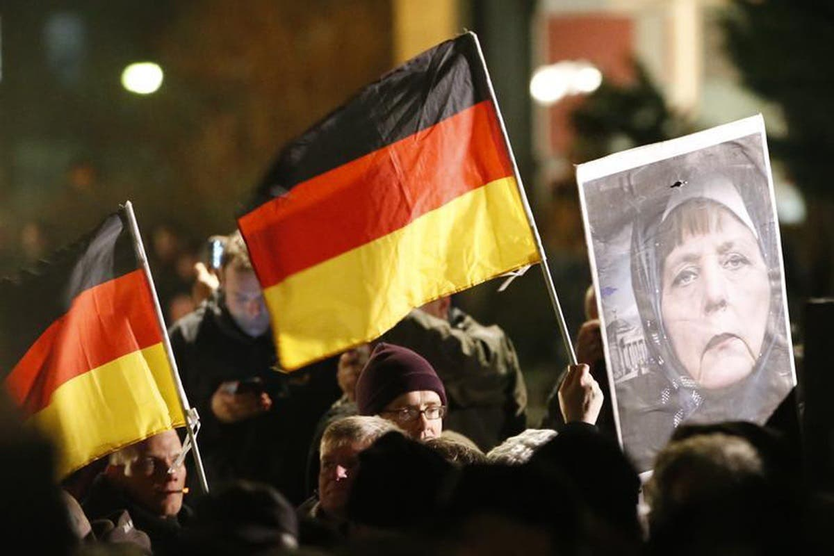 Supporters of anti-immigration movement Patriotic Europeans Against the Islamisation of the West (PEGIDA) hold German flags and a portrait depicting German Chancellor Angela Merkel during a demonstration in Dresden on Jan. 12 (Reuters)
