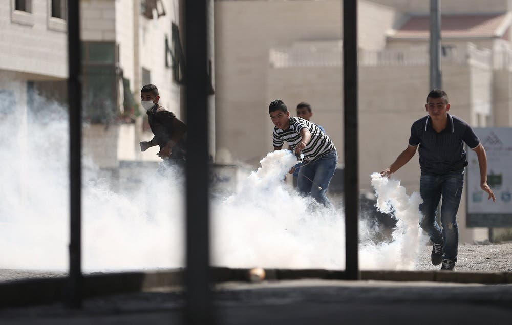 Palestinians prepare to return tear gas canisters fired by Israeli troops during clashes at a protest against an Israeli police raid on September 15, 2015. (Reuters/Mohamad Torokman TPX)