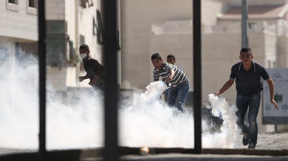 Palestinians prepare to return tear gas canisters fired by Israeli troops during clashes at a protest against an Israeli police raid on Jerusalem's al-Aqsa mosque, in the occupied West Bank town of Al-Ram, near Jerusalem September 15, 2015. Israeli police armed with stun grenades and tear gas clashed with rock-throwing Palestinian youths who barricaded themselves inside Jerusalem's al-Aqsa mosque on Tuesday, police and witnesses said, in the third day of violence at the sacred site. Masked Palestinians hurled flares at the security forces, who said they were trying to secure the plaza outside Islam's third holiest shrine to stop what they said was a Palestinian attempt to disrupt visits to the compound on Jewish New Year. REUTERS/Mohamad Torokman TPX