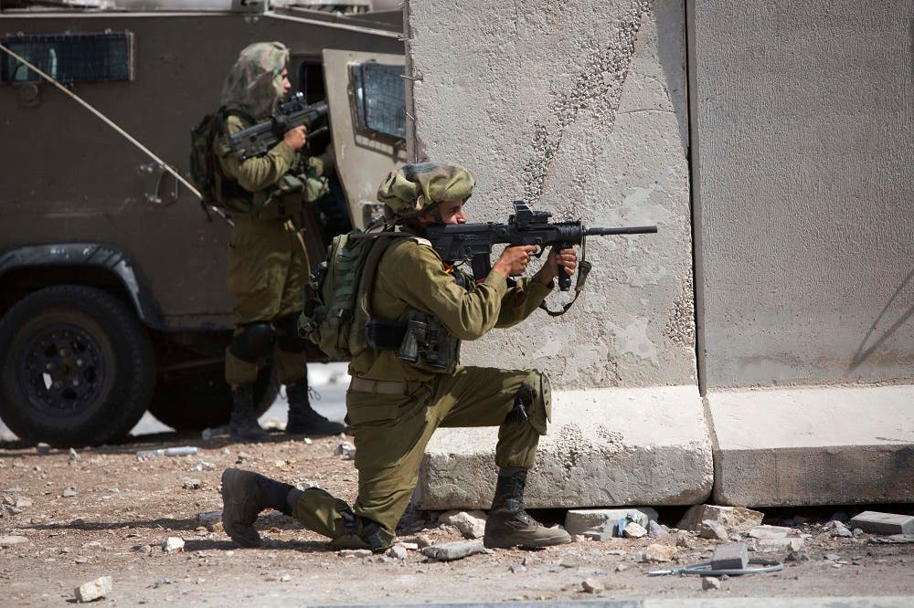 An Israeli soldier aims his weapon towards Palestinians following a demonstration in solidarity with protesters at the Al-Aqsa mosque compound in Jerusalem's Old City, during clashes in the West Bank town of al-Ram, north of Jerusalem, Tuesday, Sept. 15, 2015. Israeli police clashed with Palestinian protesters Tuesday in a third straight day of unrest at Jerusalem's most sensitive holy site. (AP Photo/Majdi Mohammed)