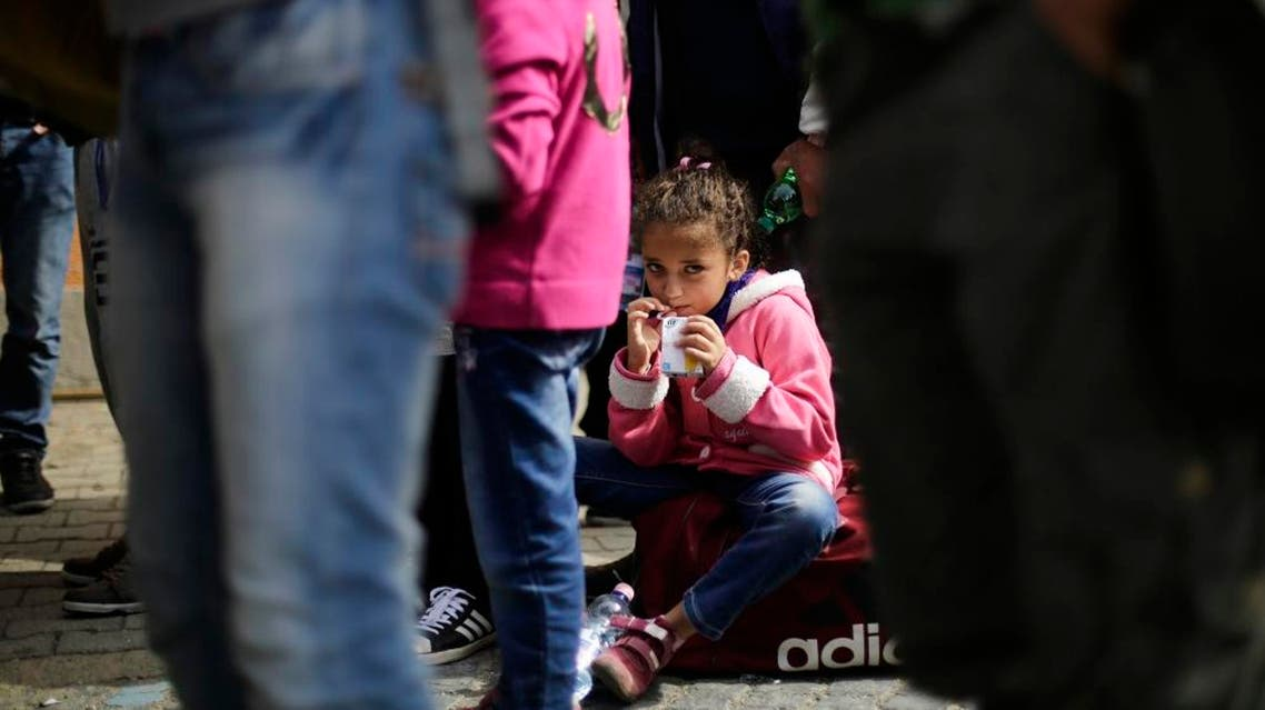 A girl drinks some juice after she arrived with other refugees at the train station of the southern German border town Passau, Tuesday, Sept. 15, 2015, after they have been taken off a train by German border police for registration. Germany introduced temporary border controls Sunday to stem the tide of thousands of refugees streaming across its frontier, sending a clear message to its European partners that it needs more help with an influx that is straining its ability to cope. (AP Photo/Markus Schreiber)